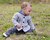 Child sitting on grass — Stock Photo