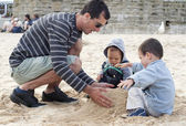 Father and children building sandcastle — Stock Photo