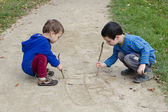 Children drawing into sand — Stock Photo