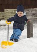 Winter child with snow shovel — Stock Photo