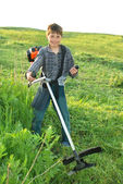 Junior benzokosoy mower with grass on the workpiece — Stock Photo