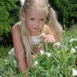 Girl smelling a flower on the meadow — Stock Photo