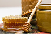 Honey in pot, honeycomb and stick — Stock Photo