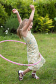 Little girl playing with hula hoop — Stock Photo