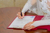Married couple signing marriage registration form — Stockfoto