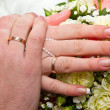 Hands and rings on wedding bouquet — Stock Photo #25462523