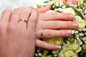 Ręce i pierścienie na bukiet ślubny — Zdjęcie stockowe