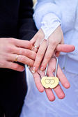 Padlock in the hands of the newlyweds — Stock Photo