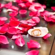 Wedding rings surrounded by rose petals — Stock Photo