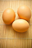 Chicken eggs on a wooden mat — Stock Photo