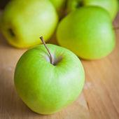 Grüne äpfel auf einem holzbrett — Stockfoto