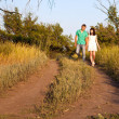 Happy young couple walking on a path in the woods — Stock Photo