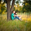 Young loving couple sitting under a tree — Stock Photo