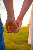Young beautiful stylish couple in love holding hands — Stok fotoğraf