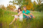 Portrait of young romantic couple sitting in forest enjoying — Stock Photo