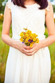 Bouquet of wild flowers in the bride's hands — Stock Photo
