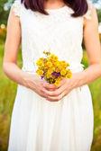 Bouquet of wild flowers in the bride's hands — Stock Photo
