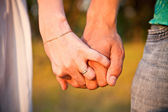 Young beautiful stylish couple in love holding hands — Stock Photo