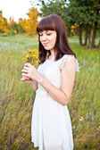 Young girl with a bouquet of wild flowers — Stockfoto