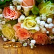 Gold rings next to a wedding bouquet — Stock Photo