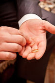 The groom holds the wedding ring on the hand — Stock Photo