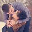 Young couple kissing in the winter forest — Stock Photo
