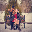 Love couple sitting on a bench in winter park — Stock Photo