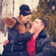 Stock Photo: Love couple sitting on a bench in winter park