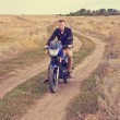 Stock Photo: Man with a motorcycle on a country road