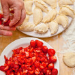Woman sculpts dumplings with strawberries  — Stock Photo