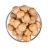Walnuts in a glass dish on a white background — Stok fotoğraf