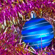 Blue Christmas ball on a background of defocused tinsel — Photo
