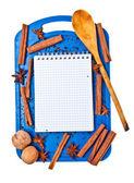 Open Kladblok en specerijen op een blauwe snijplank — Stockfoto