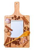 Open notepad and spices on a wooden cutting board — Stock Photo