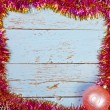 Wooden background in a frame of the Christmas tinsel — Stock Photo