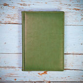 Green closed the book on wooden boards — Stock Photo