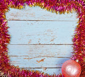 Wooden background in a frame of the Christmas tinsel — Stok fotoğraf