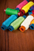 Colorful spools of thread on a wooden background — Stok fotoğraf