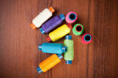 Colorful spools of thread on a wooden background — Stock Photo