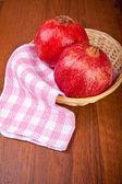 在一张小木桌上的柳条篮子里的石榴果 — 图库照片