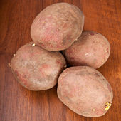 Raw potatoes on wooden background — Stock Photo
