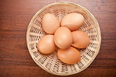 Chicken eggs in a wicker basket on the table — Stock Photo