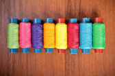 Colorful spools of thread on a wooden background — Stock fotografie