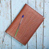 In leather-bound notebook on a wooden background — Stock Photo