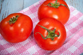 Three tomatoes on a plaid towel — Foto Stock