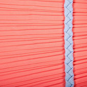 Woven textile belt on red silk background — Stock Photo