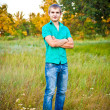 Young man standing on a meadow with his arms folded — Stock Photo