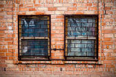 Two windows with bars on the brick wall — Foto de Stock