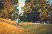 Couple in love running around in the forest glade — Stock Photo