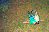 Loving couple lying on the grass, top view — Stock Photo